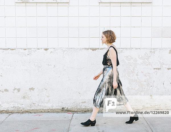 Auf der Straße gehende Frau im Metallrock  in voller Länge  Seitenansicht