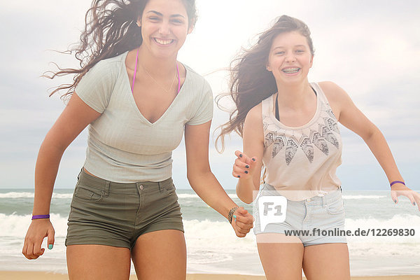 Portrait of two teenage girls on beach  smiling