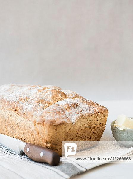 Frisch gebackener Vollkornbrotlaib mit Messer und Butter