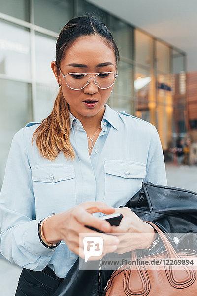 Porträt einer Geschäftsfrau im Freien  mit Smartphone  nachdenklicher Ausdruck