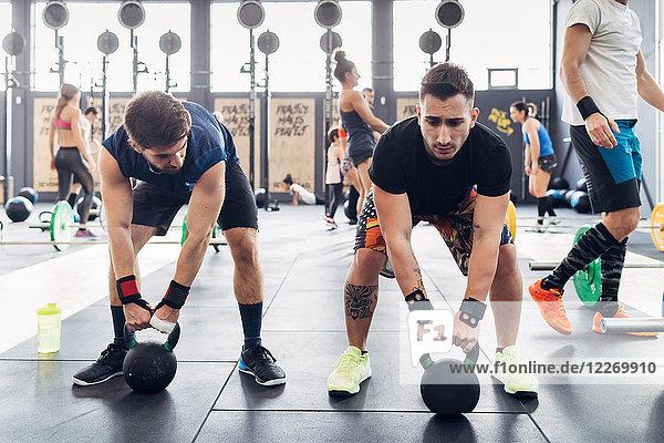 Gewichtheben von Männern mit Kesselglocken im Fitnessstudio