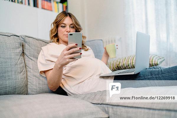 Schwangere Frau auf dem Sofa mit Laptop und Smartphone