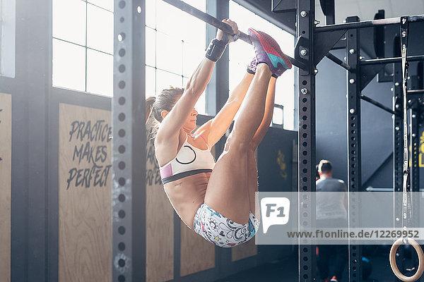 Frau benutzt Klimmzugstange im Fitnessstudio