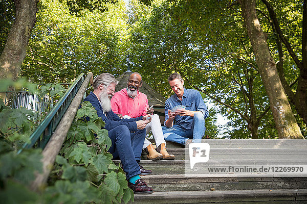 Drei reife Männer  im Freien  auf Stufen sitzend  Karten spielen  niedriger Blickwinkel