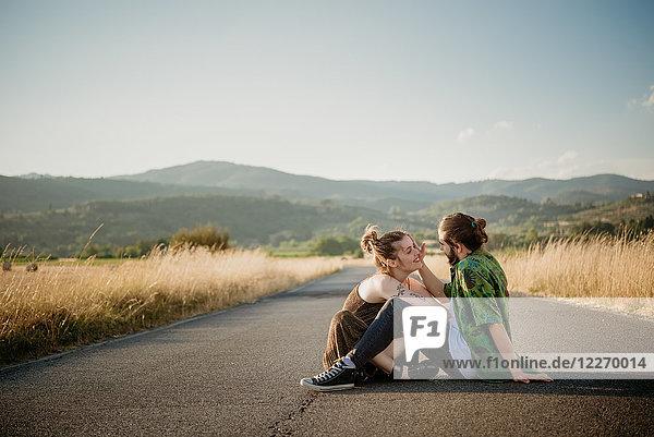 Paar auf der Straße durch goldenes Grasfeld  Arezzo  Toskana  Italien