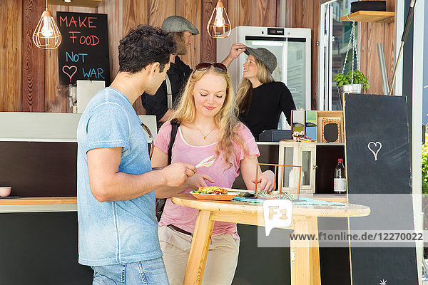 Customers enjoying meal at food truck