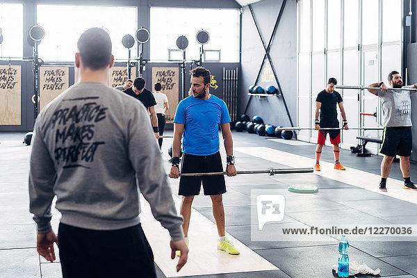Gruppe von Personen beim Gewichtheben im Fitnessstudio
