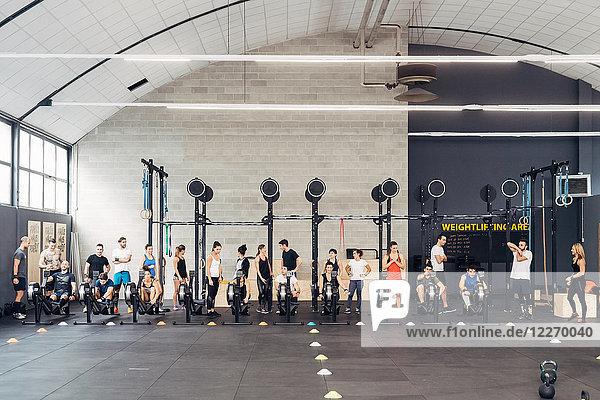 Große Gruppe von Menschen trainiert im Fitnessstudio