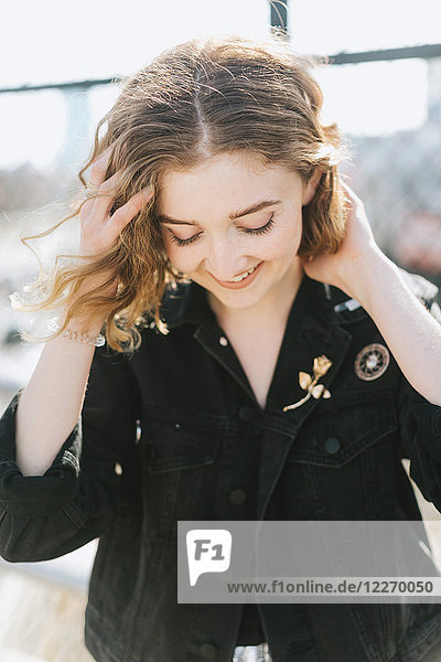 Porträt einer Frau in Jeansjacke mit Anstecknadeln  die lächelnd nach unten blickt