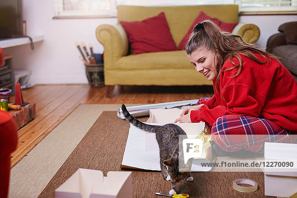 Young woman sitting on living floor wrapping gifts and watching cat