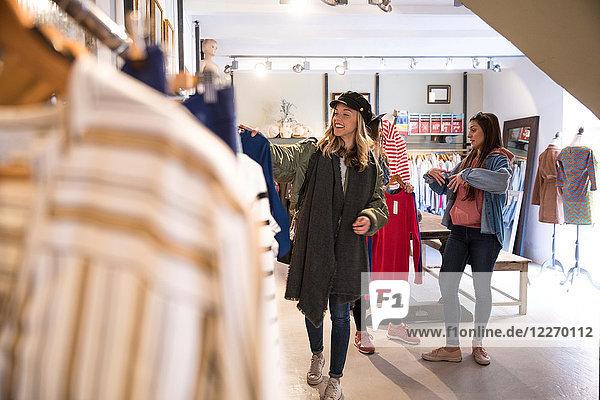 Drei Freunde  einkaufen  Kleider auf der Schiene im Geschäft anschauen
