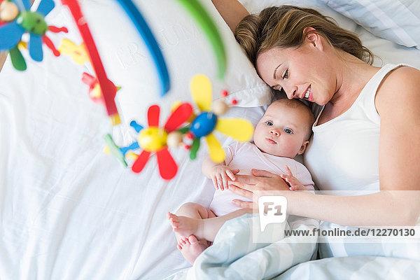 Mutter und Baby im Bett  Blick auf Krippenkarussell