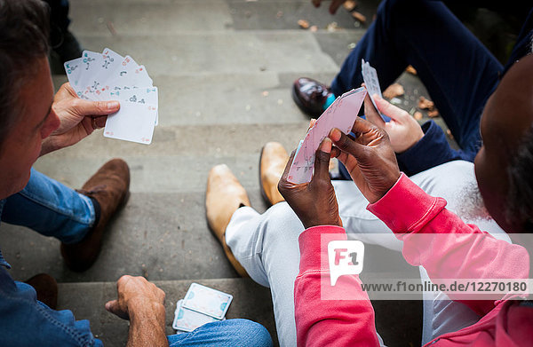 Drei reife Männer  im Freien  auf Stufen sitzend  Karten spielen  erhöhte Ansicht