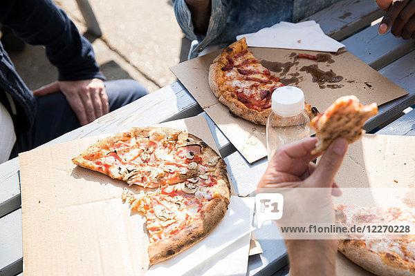 Freunde essen Pizza im Freien
