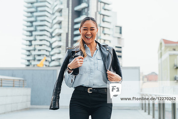 Portrait of businesswoman outdoors  wearing leather jacket around shoulders  laughing