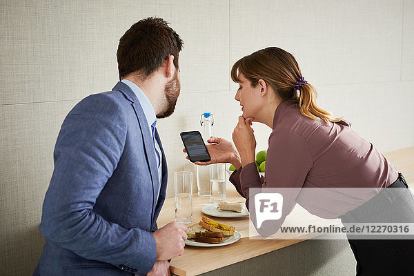 Colleagues having lunch  looking at smartphone