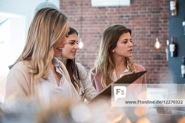 Drei Freundinnen  die im Café am Tresen stehen