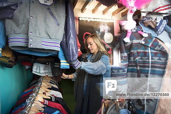 Junge Frau stöbert in einem Secondhand-Laden nach Vintage-Kleidung