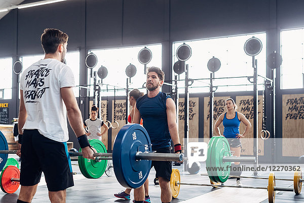 Men weightlifting with barbells in gym