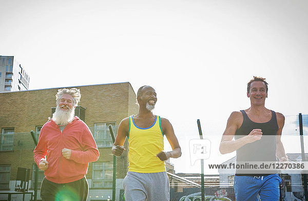 Drei reife Männer  im Freien  joggend  niedriger Blickwinkel