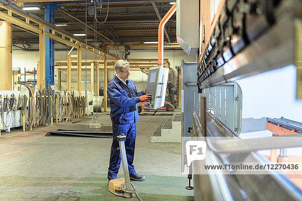 Engineer operating steel bending machine in engineering factory