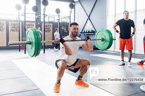Mann Gewichtheben Langhantel im Fitnessstudio