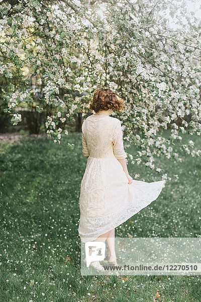 Frau wirbelt am Blütenbaum