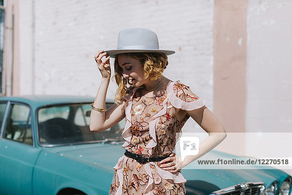 Woman wearing hat by vintage car