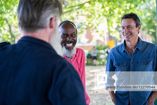 Drei reife Männer  draußen  im Gespräch