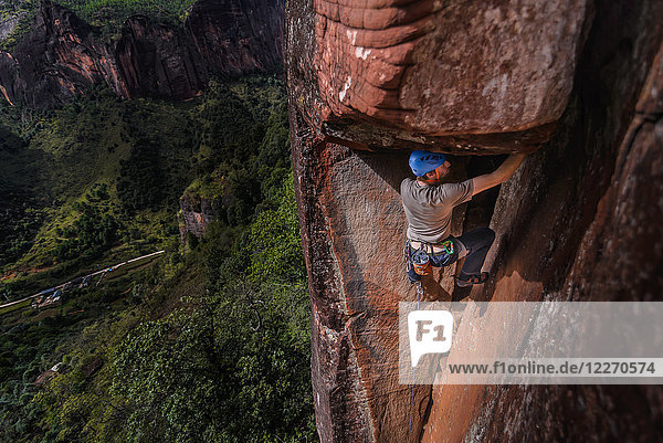 Rock climber climbing sandstone rock  elevated view  Liming  Yunnan Province  China