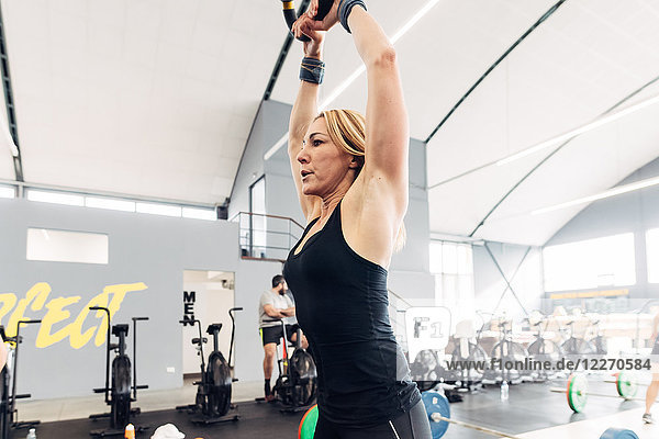 Gewichtheben einer Frau mit Kesselglocke im Fitnessstudio