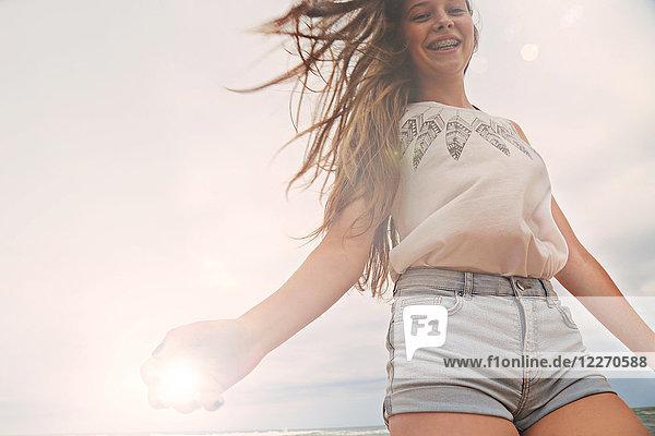Porträt einer Teenagerin am Strand  lächelnd  Blick aus niedrigem Winkel
