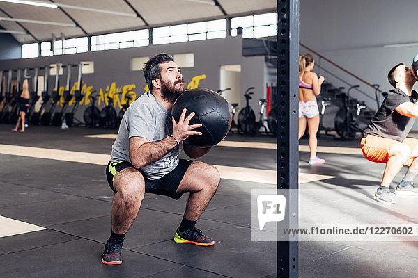 Mann in Turnhalle mit Medizinball