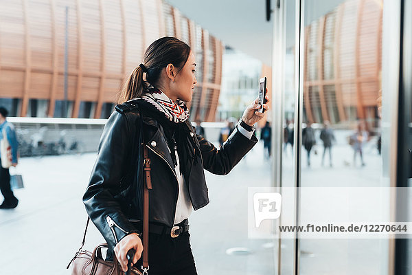 Woman outdoors  using smartphone  carrying luggage