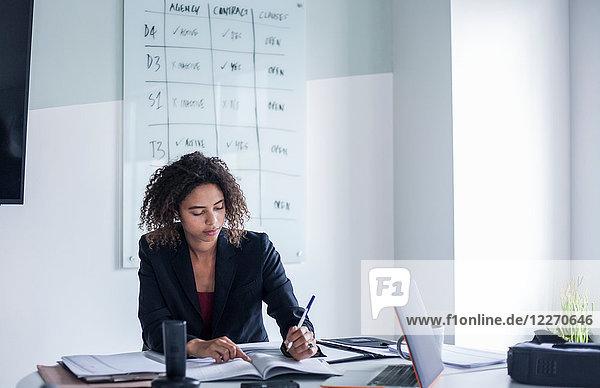 Geschäftsfrau am Schreibtisch beim Schreiben im Büro