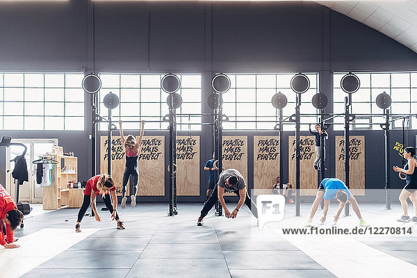 Group of people exercising in gym  bending forwards