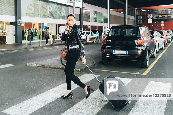 Frau geht im Freien spazieren  zieht Rollkoffer  spricht über Smartphone