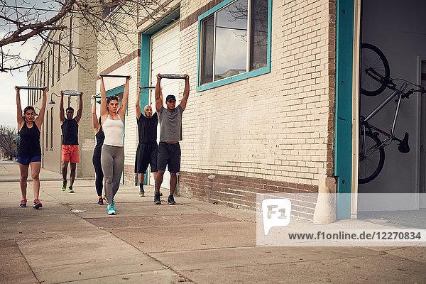 Gruppe von Personen mit erhobenen Armen  die Gewichte tragen  Frontansicht