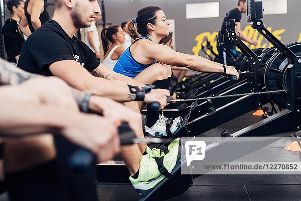 Große Gruppe von Menschen benutzt Rudergerät im Fitnessstudio