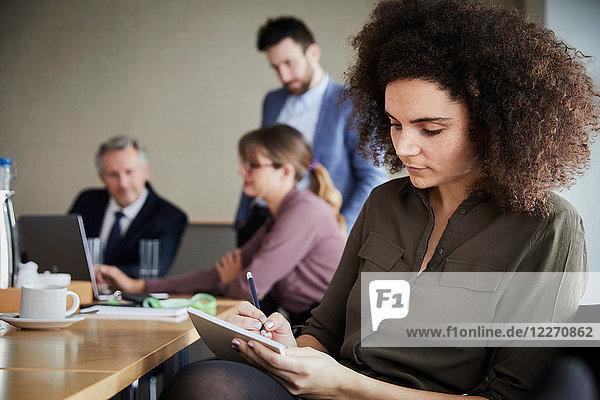 Geschäftsfrau im Büro schreibt auf Notizblock