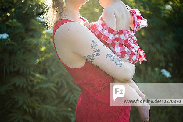 Frau und kleines Mädchen im Garten