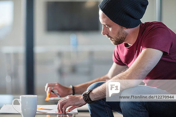 Young man making notes during coffee break in office