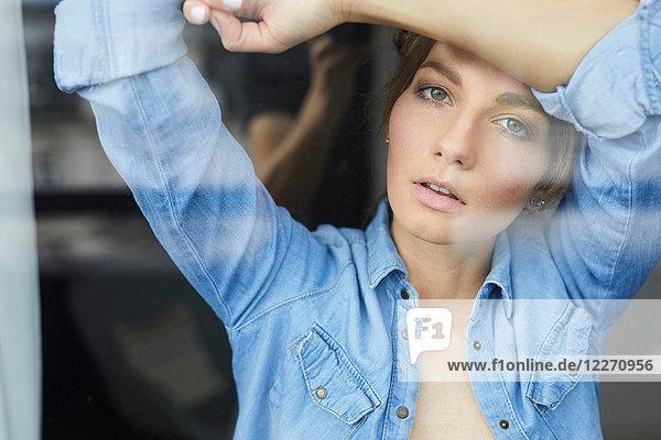 Düstere junge Frau beim Blick durchs Fenster  Porträt