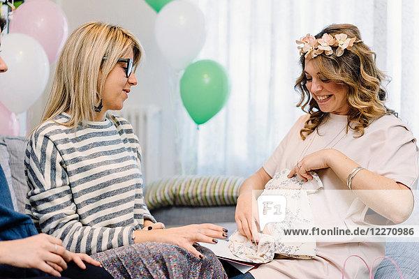 Schwangere und Freundinnen auf dem Sofa beim Betrachten des Babykleides