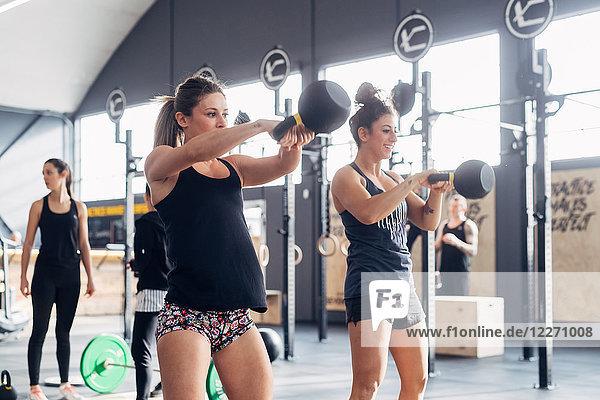 Gewichtheben von Frauen mit Kesselglocken im Fitnessstudio