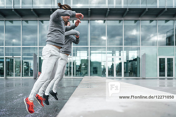 Young adult male twins training  jumping onto wall in city