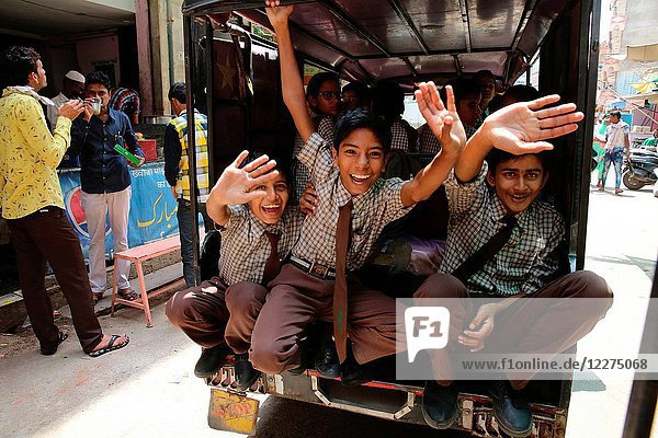 Ajmer schoolboys waving from a vehicle. India.