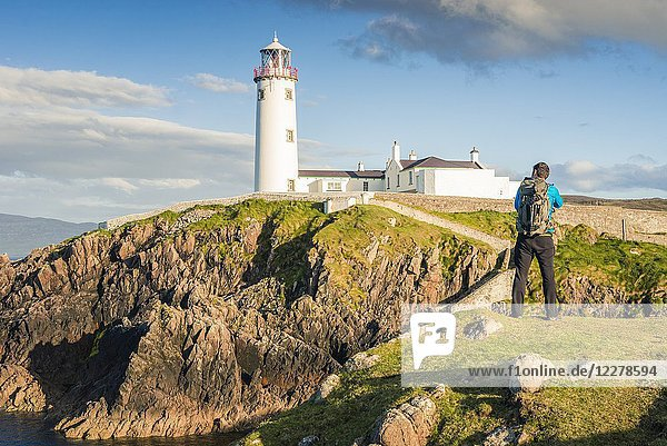 Fanad Head (Fánaid) lighthouse,  County Donegal,  Ulster region,  Ireland,  Europe. A photographer on the field near the Fanad Head lighthouse.