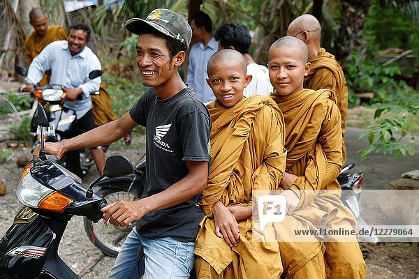 Young Cambodian monks traveling on scooters in Battambang province. Cambodia.