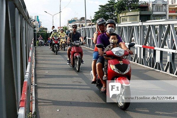 Vietnamese Vietnamese family on motorbike. Road traffic. Ho Chi Minh City. Vietnam.